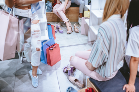 Cropped image of three attractive young girls are doing shopping with shopping bags in shoes store in in modern mall.