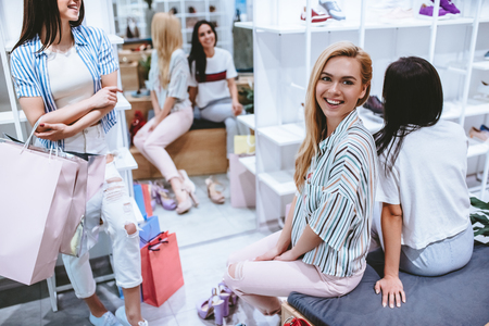 Three attractive young girls are doing shopping with shopping bags in shoes store in in modern mall. Imagens