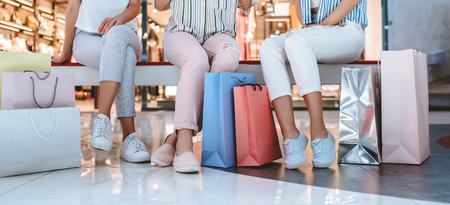 Cropped image of three attractive young girls are doing shopping with shopping bags in modern mall.