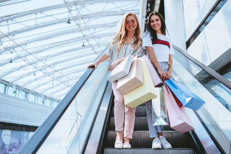 Two attractive young girls are doing shopping with shopping bags in modern mall.