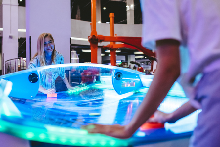 Attractive young women are having fun in amusement park. Playing table hockey together.