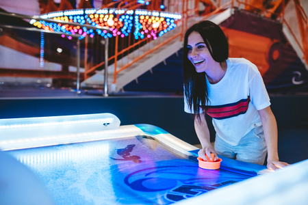 Attractive young woman is having fun in amusement park. Playing table hockey. Stock Photo