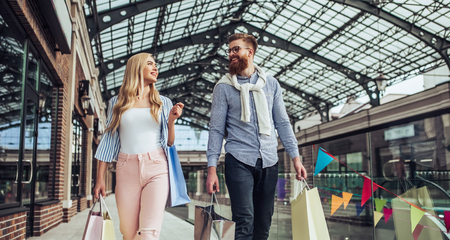 Stylish young couple is spending time together outdoors. Happy couple  is walking with shopping bags and doing shopping in the city. Attractive woman and handsome bearded man are having fun together. Stock Photo