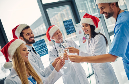 Merry Christmas and Happy New Year! Group of doctors celebrating winter holidays at work. Medical personnel in uniform and Santa Claus hats drinking champagne together.