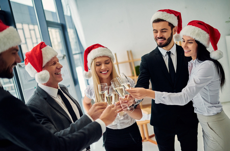 Merry Christmas and Happy New Year! Group of office workers celebrating winter holidays together at work. Business people drinking champagne in office.