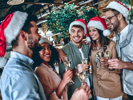 ¡Feliz Navidad y próspero año nuevo 2020! Los jóvenes creativos multirraciales están celebrando las vacaciones en la oficina moderna. Grupo de jóvenes empresarios beben champán en coworking. Exitoso equipo hipster de autónomos.
