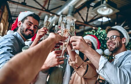 Merry Christmas and Happy New Year 2020!Multiracial young creative people are celebrating holiday in modern office. Group of young business people are drinking champagne in coworking. Successful hipst 写真素材