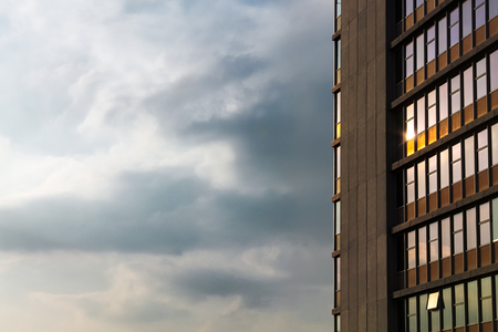 Geometrical composition of concrete building with windows reflecting sunset lighting Stock Photo