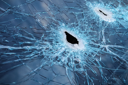 Closeup of a whole and cracked windshield produced by gunshots