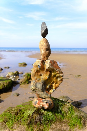 Sculpture made from stones on a beach with sea in background Stock Photo