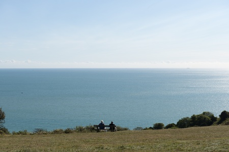 Stunning view of the English Channel looking over coastal hills   Two seniors in the mid ground sitting on a bench enjoying the view Stock Photo