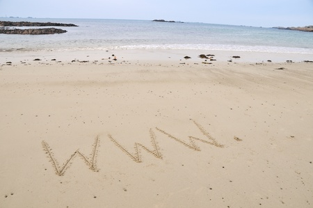 www written in sand with sea in distance