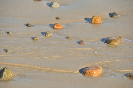 multi coloured pebbles on a sandy golden beach with water ripples Stock Photo