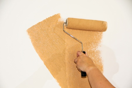 Female hand roller painting a white wall Stock Photo
