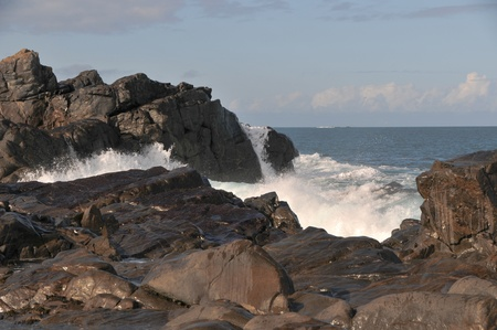 Waves crashing against rocks in Guernsey photo