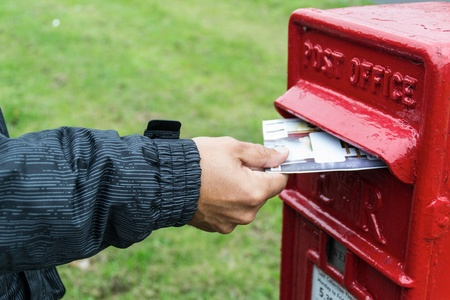 Posting a letter in a red post box