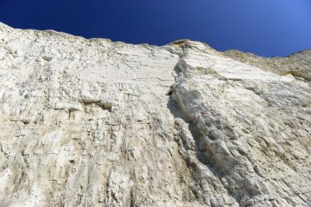 A chalky white cliff face against a blue sky
