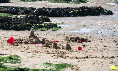 Sand castles on a sandy beach with sea weed covered rocks Stock Photo