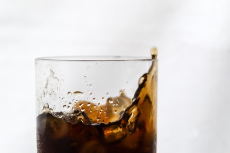 A glass of Cola with ice splashing against a white background Stock Photo - 16853742