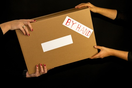 Brown box delivered by hand against a black background photo