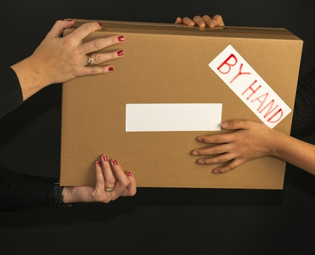 Brown box delivered by hand against a black background
