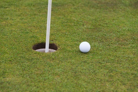 golf ball close to a hole with the flag in place photo
