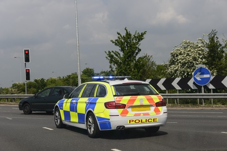British Police car on emergency call at a round about Editorial
