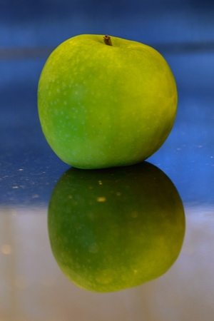 Green apple with reflection on a black granite work top Stock Photo