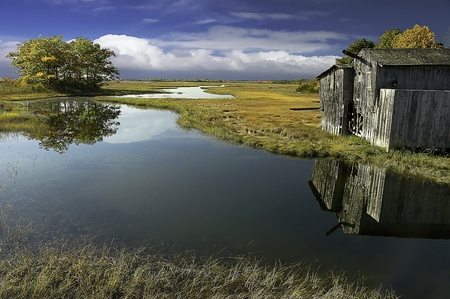 watershed: as the tides move in and out of the marsh lands, reflecions of the shack on the lands, shimmers in the daylight