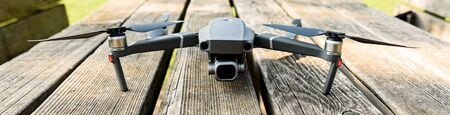front view of a drone ready to fly leaning on a wooden table at the park