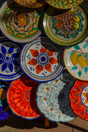 Various decorated pottery dishes hung for sale outside a souvenir shop in Lipari, Sicily