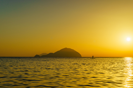 lone paddle board surfer at sunset Stock Photo