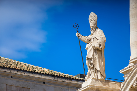 ortigia: The statue of St. Peter and some baroque elements in the external facade of the Cathedral of Syracuse