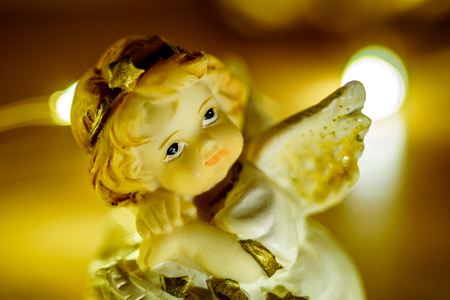 retro christmas: Angel statue with lights in background