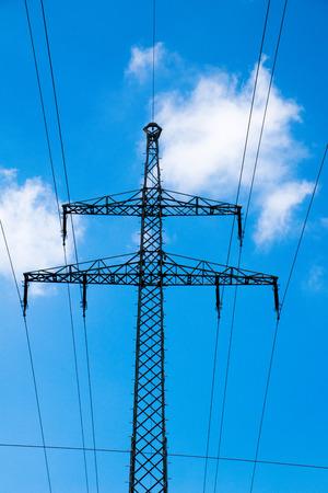 high voltage current: Electricity Pylon against blue sky