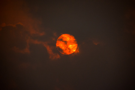 red sun behind clouds