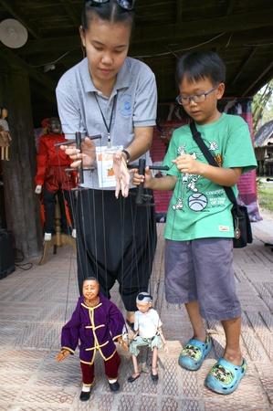hoon: CHIANG MAI THAILAND-FEB. 23 : ASEAN Enchanting Puppets 2013.Unidentified woman and child play identity Hoon sai Sema Marionettes of Thailand at CMU. Art Center.on FEB. 23,2013 in Chiangmai,Thailand