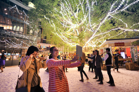 chiangmai: CHIANGMAI THAILAND - DEC. 22 : Nimman Snow Festival. Unidentified women shooting selfie festival with beautiful decorative lighting at Nimman neighbourhood. on Dec. 22, 2014 in Chiang Mai, Thailand Editorial