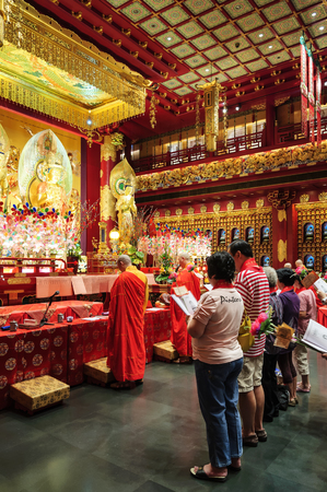 adulation: SINGAPORE CITY, SINGAPORE - FEB. 4, 2012 : BUDDHA TOOTH RELIC TEMPLE, Unidentified tourists to worship at this temple is always first and one of the attractions with beautiful architecture. Editorial