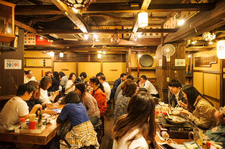 TOKYO JAPAN - MARCH 29, 2018 : Shinjuku neighborhood, After work Japanese people gather to eat and drink fun. interior of the restaurant is simply decorated in a unique contemporary Japanese style. Redakční