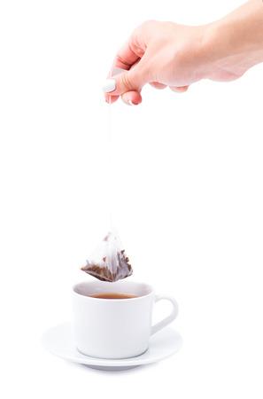 tea bag: Hand with a tea bag on a white background