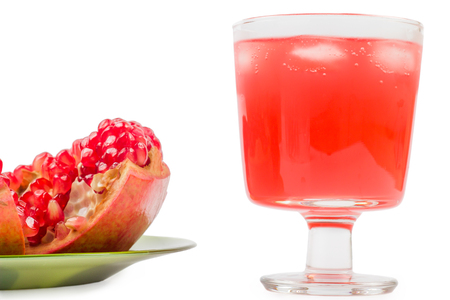 pomegranate in a plate broken and lemonade with ice on a white background Stock Photo