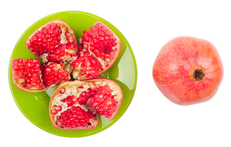 pomegranate in a plate broken on a white background Stock Photo
