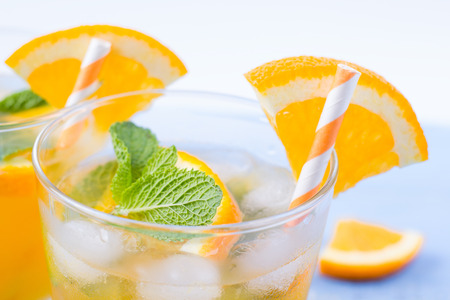 sweet segments: Drink orange with ice in glasses, on a table