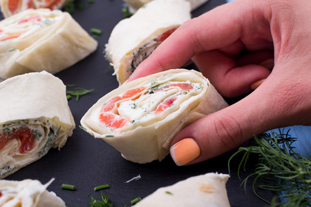 fresh food fish cake: Roll from red fish with cheese and greens on a table
