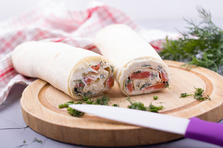 red  fish: Roll from red fish with cheese and greens on a table