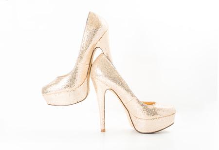 分離された白にゴールドの女性の高いヒールの靴をファッションします。