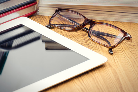 Tablet with blank screen  on office wooden table and glasses vignetting style photo