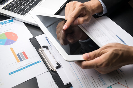 finance background: businessman working on his pc tablet Stock Photo