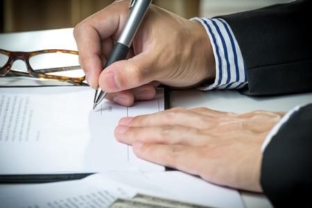firmando: hombre de negocios la firma de contrato de comercialización. Foto de archivo